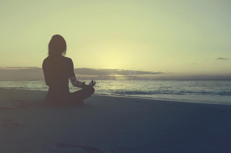 Woman practices yoga meditation lotus pose beach sunrise royalty free stock photography