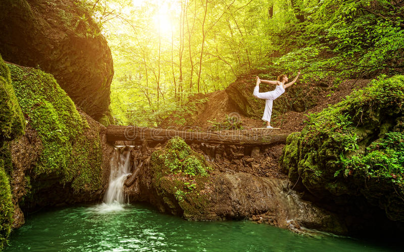 Woman practices yoga in nature, the waterfall royalty free stock photo