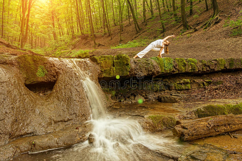 Woman practices yoga in nature, the waterfall. Urdhva phanurasana pose royalty free stock images