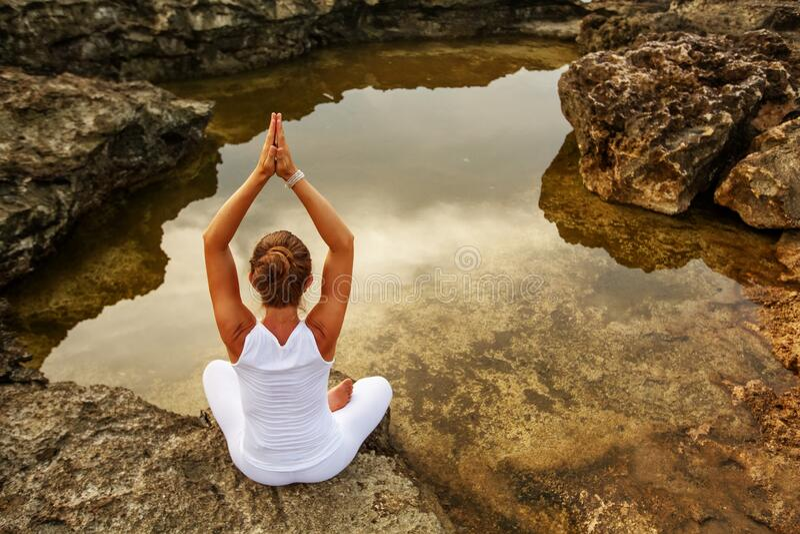 Woman practices yoga at seashore stock photo