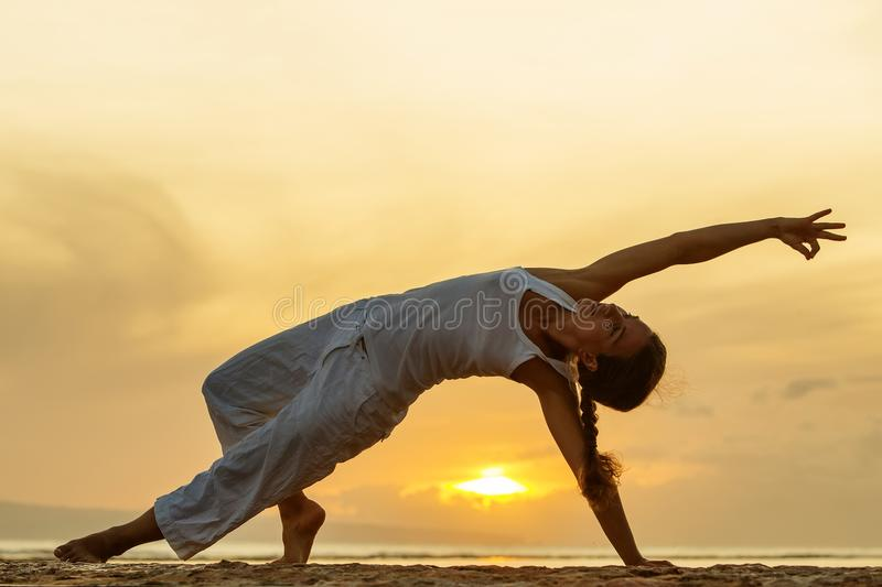 Woman practices yoga at the seashore at sunset on Bali in indonesia royalty free stock images