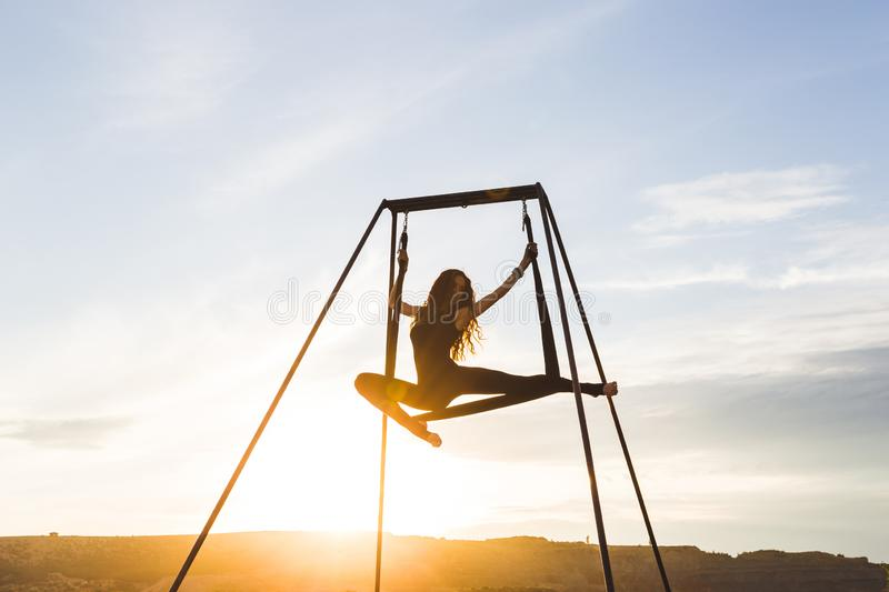 Woman practicing fly dance yoga poses in hammock outdoors at sunset stock photography