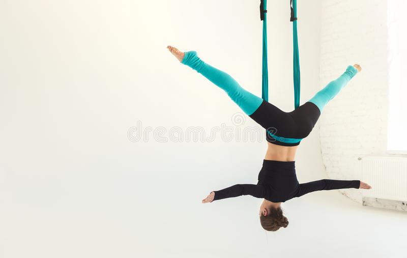 Woman practicing fly yoga over white background royalty free stock photo