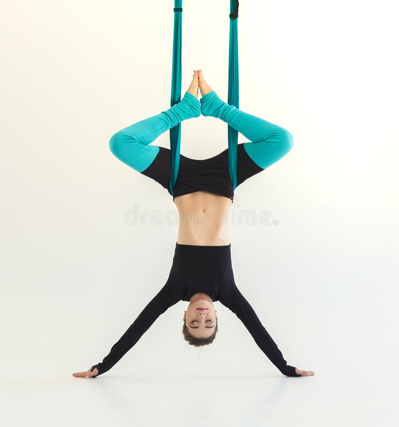 Woman practicing fly yoga over white background royalty free stock images