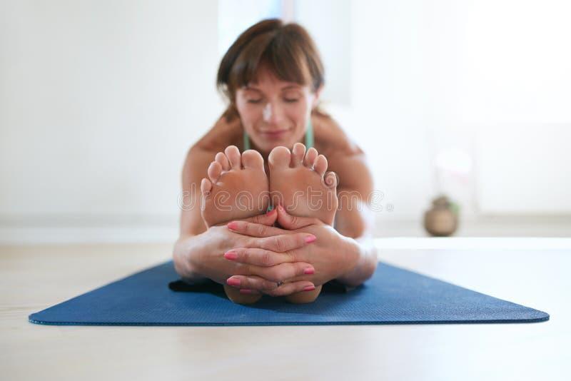 Woman practicing Paschimottanasana yoga. stock photo