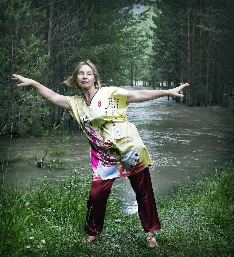 Woman practicing qigong. Portrait of a woman practicing qigong on the bank of a mountain river stock photos