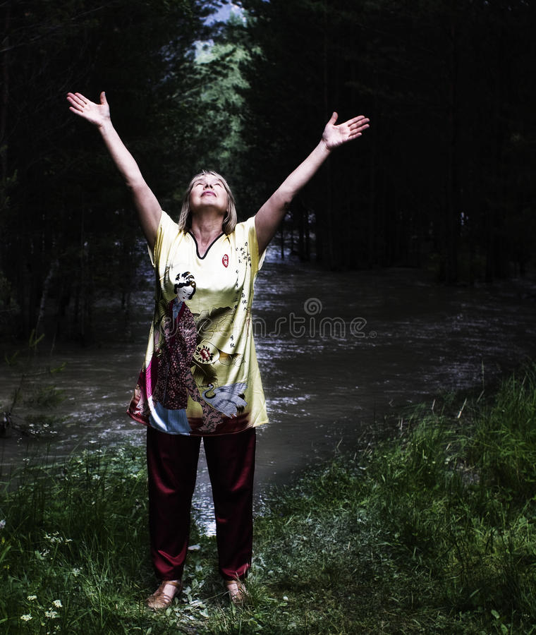 Woman practicing respiratory gymnastics. Early in the morning, on the bank of a mountain river, a woman practicing respiratory gymnastics stock photos