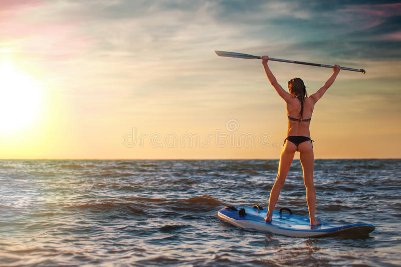 Woman practicing SUP yoga at sunset, meditating on a paddle board. royalty free stock images