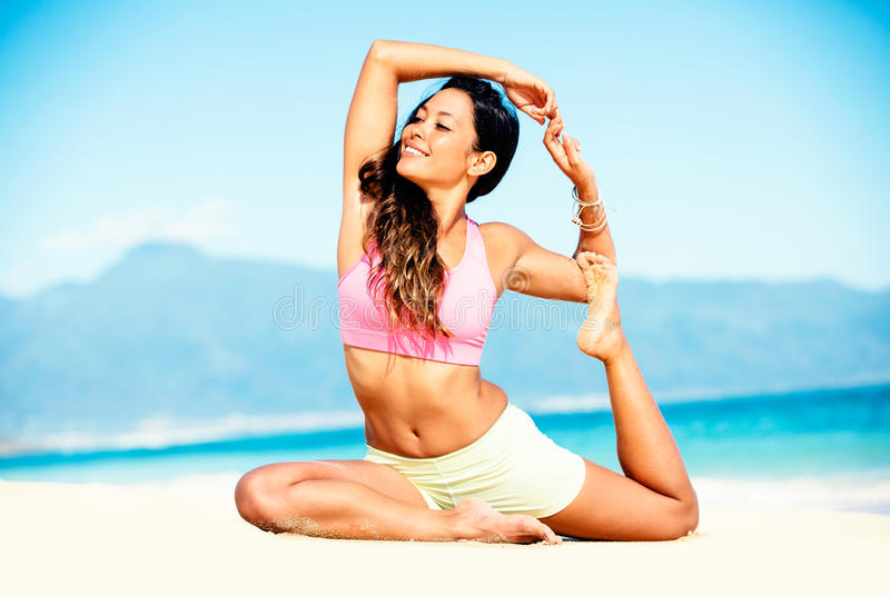 Woman practicing yoga on the beach stock images