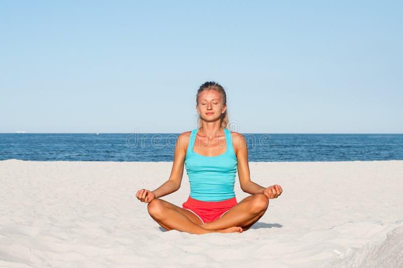 Woman practicing yoga on the beach stock photos