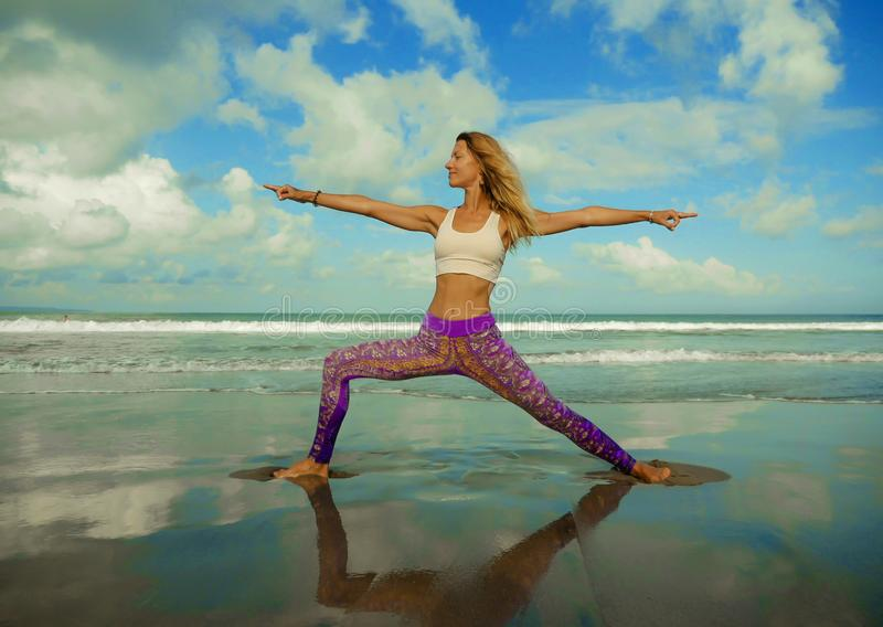 Young happy and attractive girl doing relaxation and balance exercise with sea background in wellness harmony health care and. Woman practicing yoga at beautiful royalty free stock image