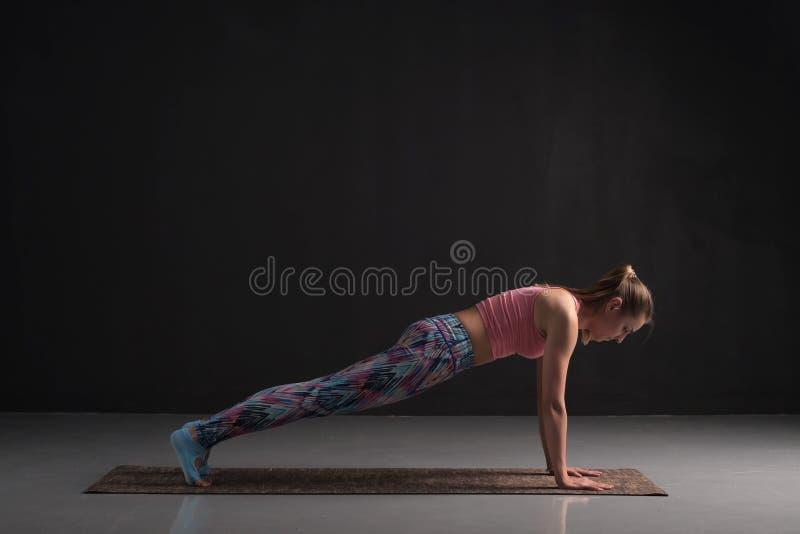 Woman practicing yoga, doing Push ups exercise, phalankasana, Plank pose. Woman practicing yoga, doing Push ups or press ups exercise, phalankasana, Plank pose stock photography