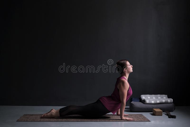 Woman practicing yoga, doing urdhva mukha svanasana, upward facing dog pose royalty free stock photos