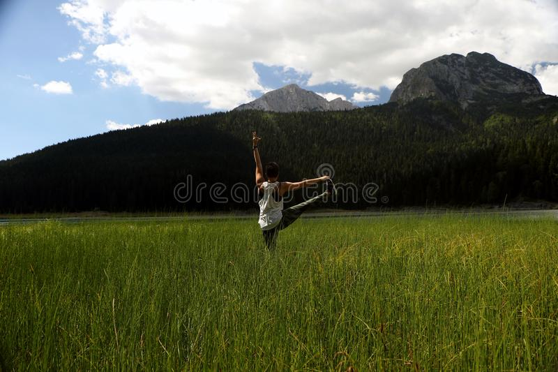 Download Woman Practicing Yoga In The Grass Stock Image - Image of meditation, lake: 103426779