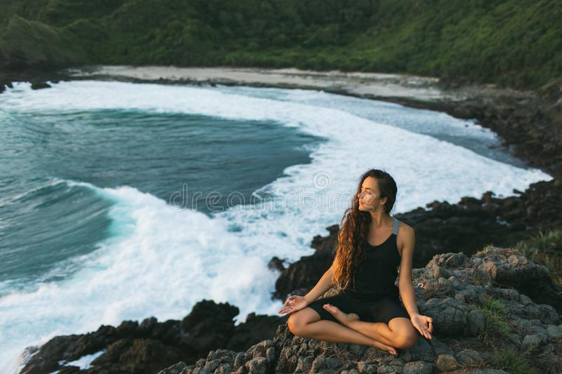 Woman practicing yoga in lotus pose at sunset with beautiful ocean view. Young woman practicing yoga in lotus pose at sunset with beautiful ocean and mountain royalty free stock image