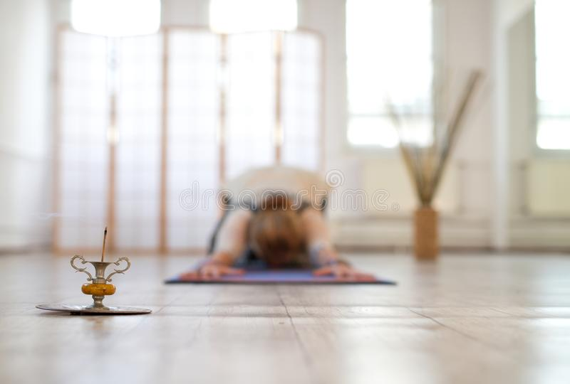 Woman practicing yoga on a mat. In the foreground you were with incense on the other woman in blur stock image