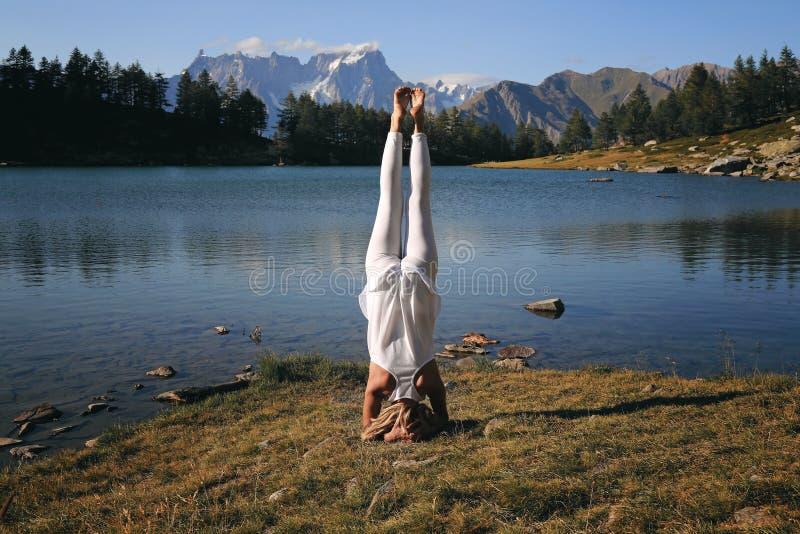 Woman practicing yoga at mountain lakeshore stock image