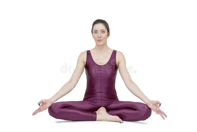 Woman practicing yoga in Muktasana pose royalty free stock photo