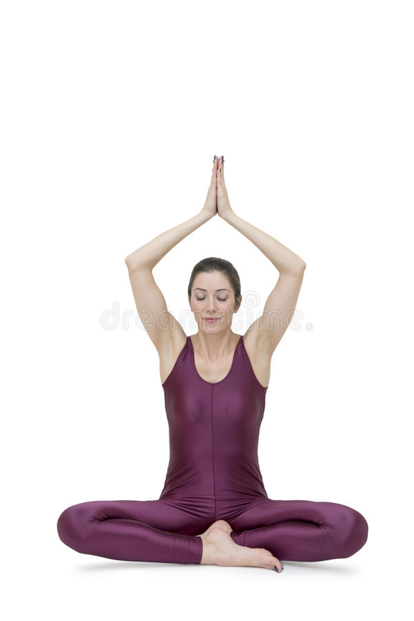 Woman practicing yoga in Muktasana pose royalty free stock photo