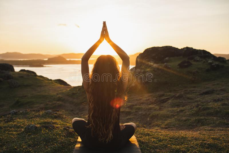 Woman practicing yoga outdoors. Spiritual harmony and well-being concept. Young woman practicing yoga outdoors. Spiritual harmony, introspection and well-being stock photos