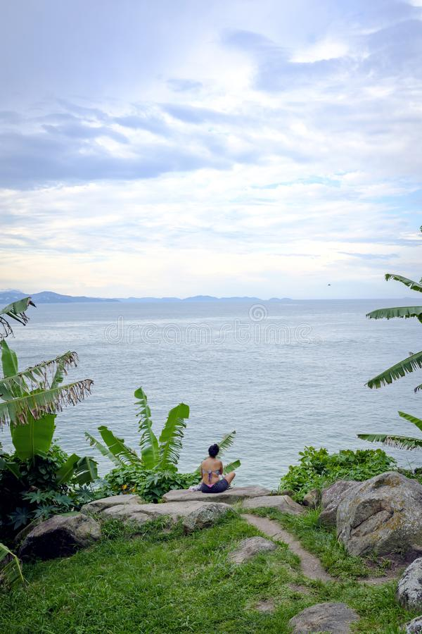 Woman practicing yoga on a rock in front of the beach royalty free stock photography