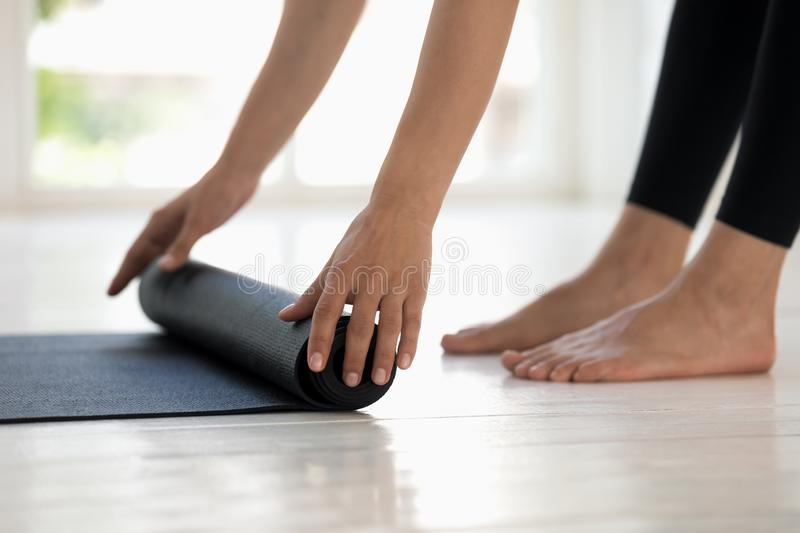 Woman practicing yoga, rolling black mat side view close up stock photo