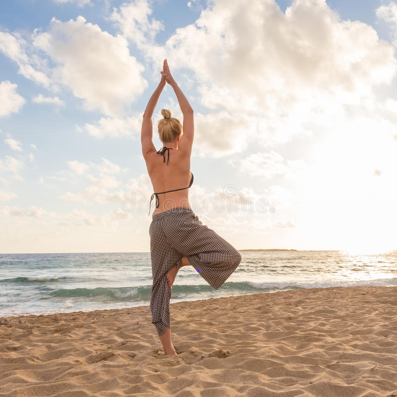 Woman practicing yoga on sea beach at sunset. Active young woman practicing yoga on beach at sunset stock photography