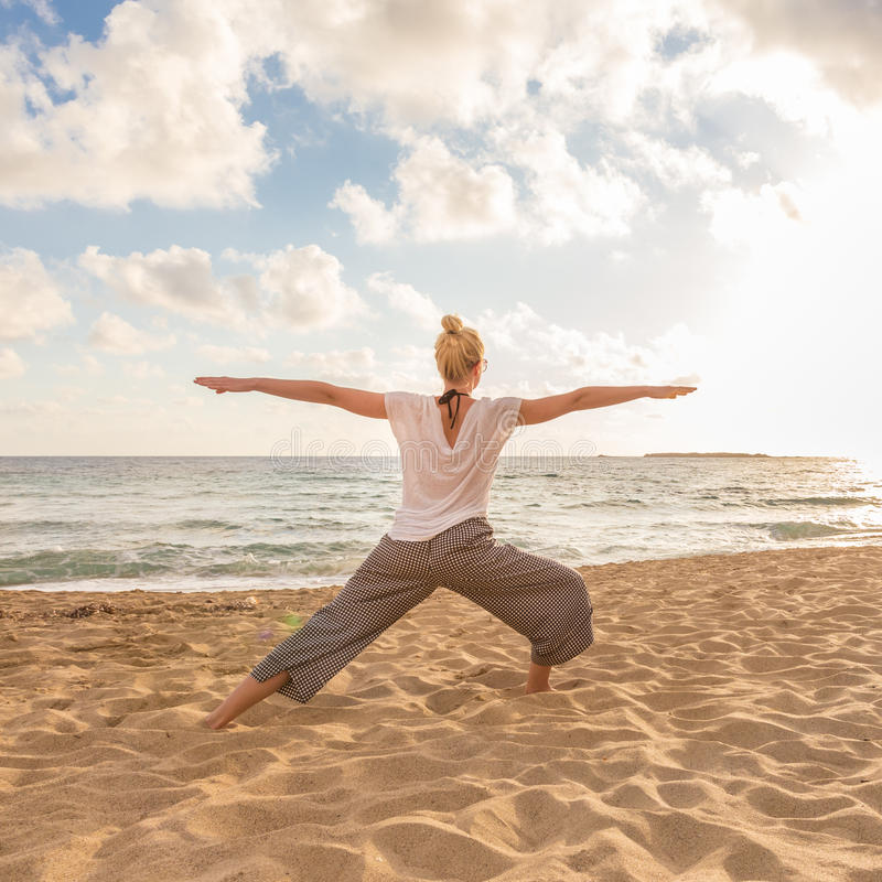 Woman practicing yoga on sea beach at sunset. Active young woman practicing yoga on beach at sunset stock photo