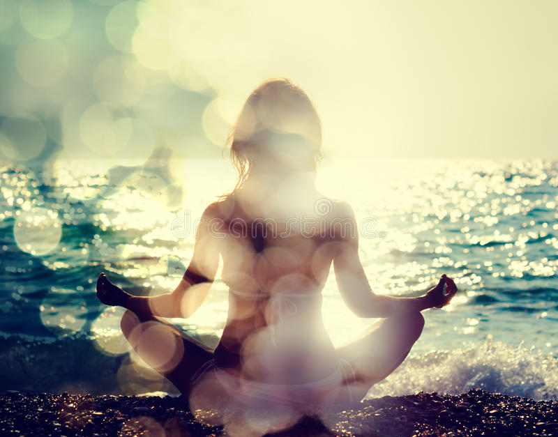 Woman Practicing Yoga by the Sea royalty free stock photography