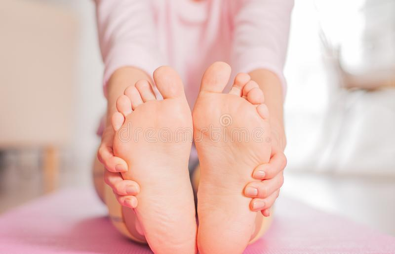Woman practicing yoga, seated forward bend pose, female feet stock image