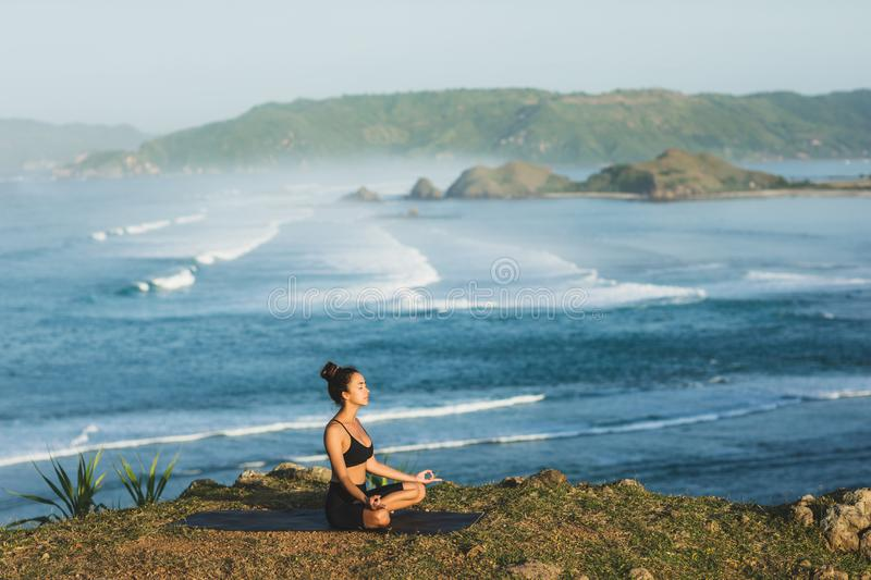 Woman practicing yoga and sitting in lotus pose outdoor with amazing ocean view. Health and well-being concept. nature background stock images
