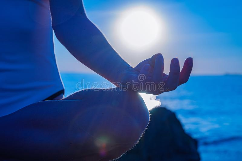 Woman is practicing yoga sitting in Lotus pose at sunrise. Silhouette of woman meditating on the beach stock photo