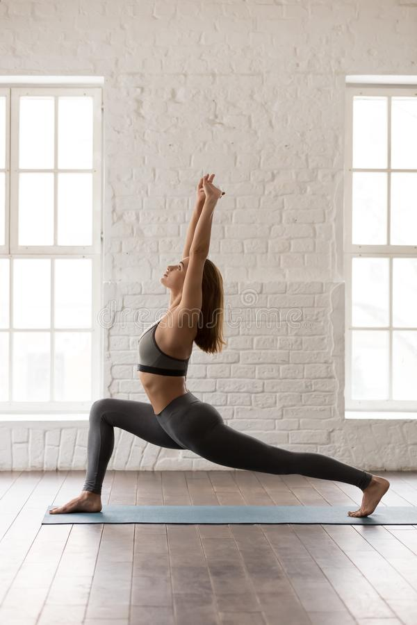 Woman practicing yoga, standing in anjaneyasana pose, Horse rider, vertical stock photos