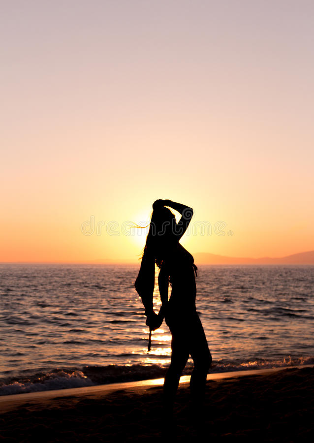 Woman practicing Yoga, sunset in the beach stock photography