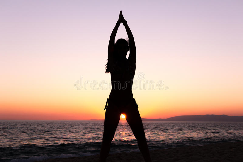 Woman practicing Yoga, sunset in the beach stock image