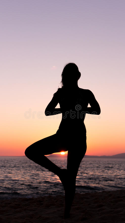 Woman practicing Yoga, sunset in the beach royalty free stock photo