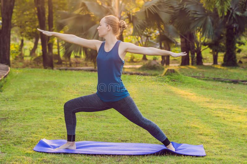 Woman practicing yoga in a tropical park royalty free stock photography
