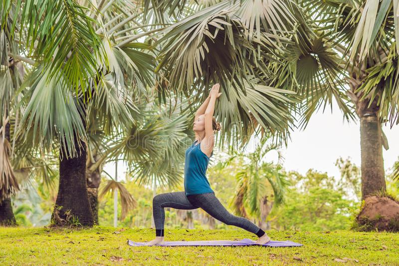 Woman practicing yoga in a tropical park royalty free stock images