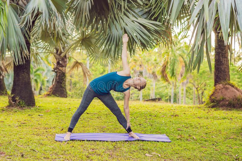 Woman practicing yoga in a tropical park stock images
