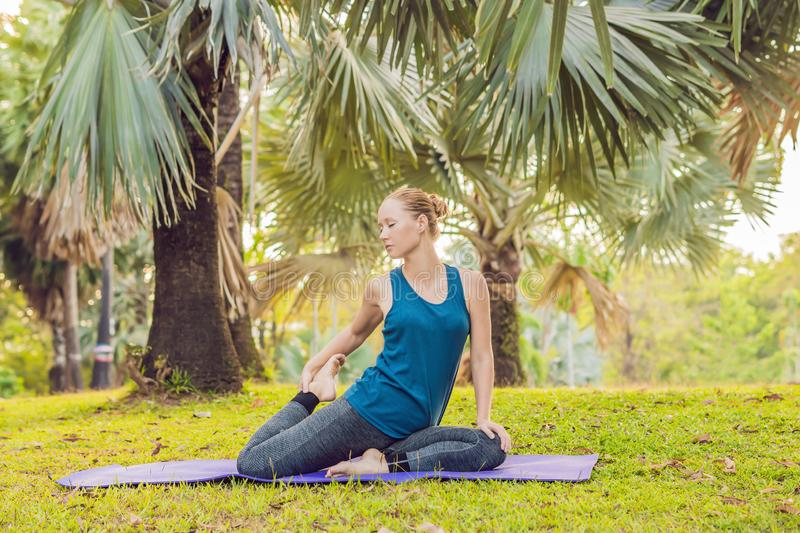 Woman practicing yoga in a tropical park royalty free stock photo