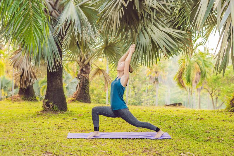 Woman practicing yoga in a tropical park stock photos