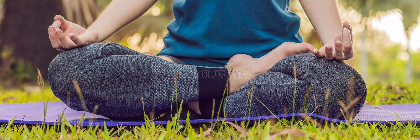 Woman practicing yoga in a tropical park BANNER, long format stock images