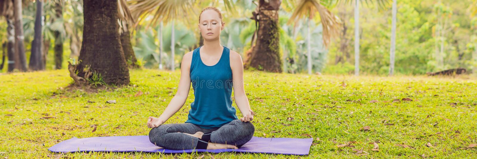 Woman practicing yoga in a tropical park BANNER, long format stock image