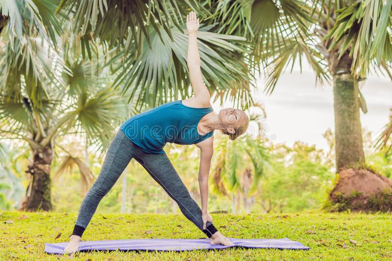 Woman practicing yoga in a tropical park stock photography