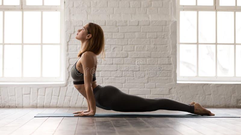 Woman practicing yoga, upward facing dog, Urdhva mukha shvanasana. Beautiful woman in grey sportswear, bra and leggings practicing yoga, stretching in upward royalty free stock photos