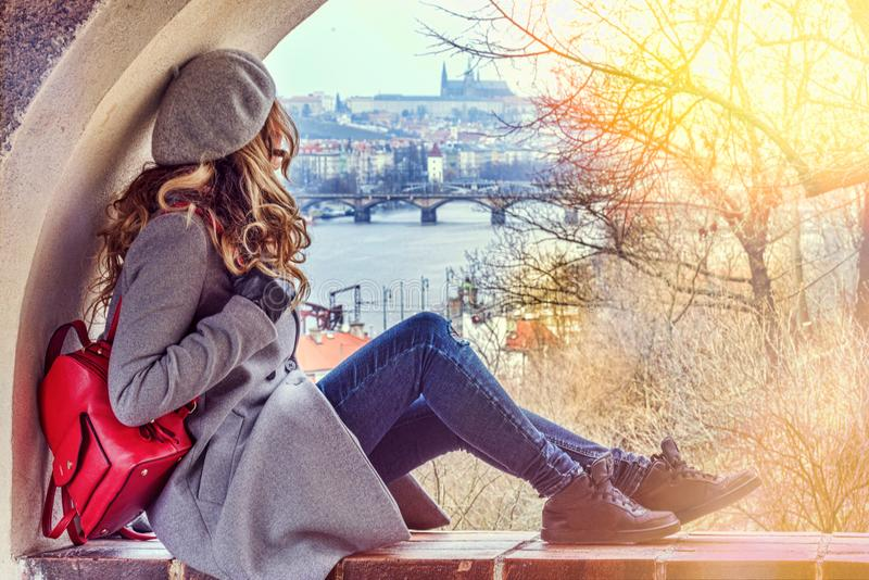 Woman in Prague, Czeh Republic. Beautiful blonde dressed in gray. Castle background views royalty free stock image