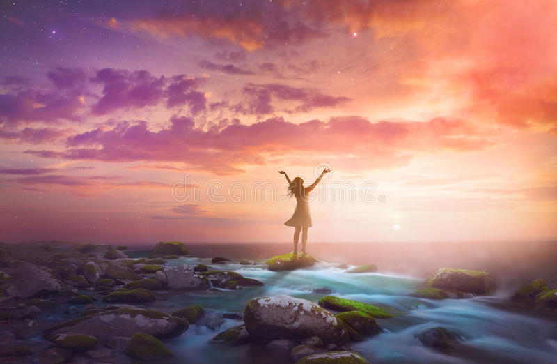 Woman praising at sunrise royalty free stock photo