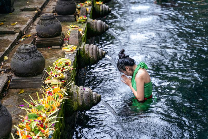 Woman pray and bath holy spring waters in Tirta Empul water temple, Bali, Indonesia. royalty free stock photos