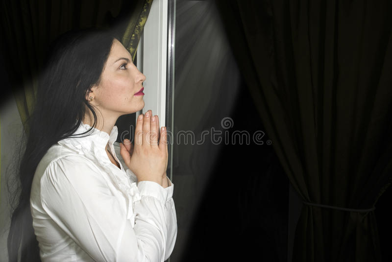 Woman prayer with faith. Woman praying in her room in the house,near the window,it;s night and a divine light shine her face,concept prayer with faith is heard royalty free stock image