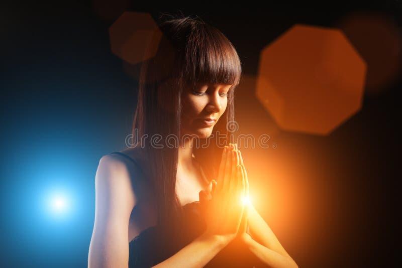 Woman praying. Beautiful young woman praying or meditating stock photo